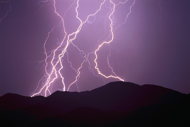 Lightning in the night sky over mountains