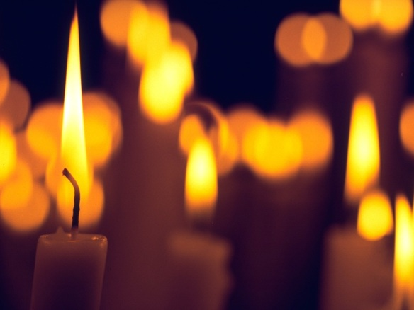 Lit candles, ascending prayers